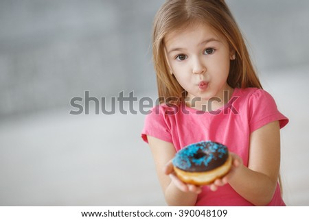 Cute kid girl eating sweet donuts. Girl holding unhealthy doughnut snack. sweets. doughnut. baby girl. child, kid  - stock photo