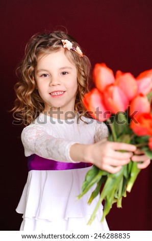 Cute kid girl holding bouquet of red tulips over red. Looking at camera.