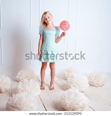 Cute kid girl holding candy in room on white - stock photo