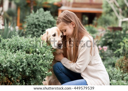 Cute kid girl holding labrador dog outdoors. Togetherness.