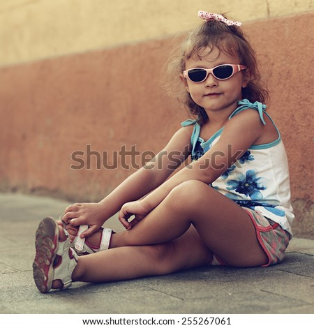 Cute kid girl in sun glasses sitting on road in town. Closeup portrait - stock photo