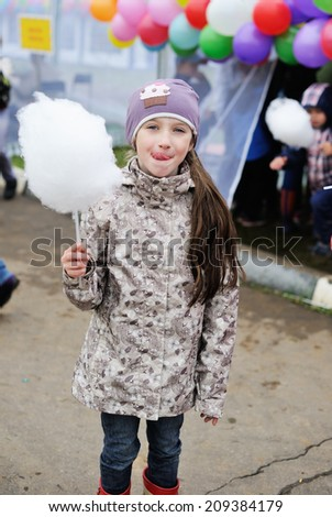 Cute kid girl in the jacket and funny hat holding cotton candy - stock photo