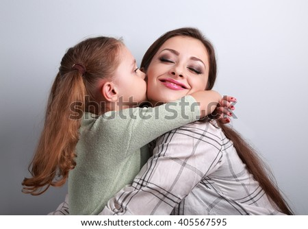Cute kid girl kissing and cuddling her enjoying beautiful mother in studio on blue background - stock photo