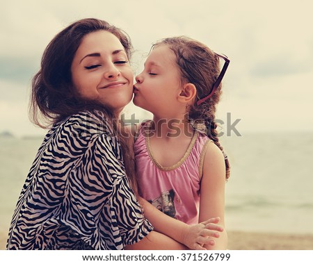 Cute kid girl kissing her happy enjoying mother with closed eyes and emotional face on sea background. Toned color portrait
