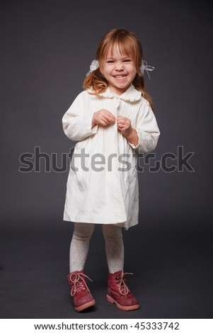 Cute kid girl posing over grey