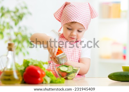 cute kid girl preparing vegetables at kitchen - stock photo