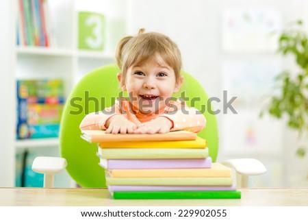 Cute kid girl preschooler with books in elementary school - stock photo