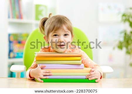 Cute kid girl preschooler with books indoor - stock photo