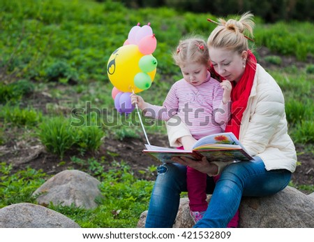Cute kid girl reading with her mother outdoor - stock photo