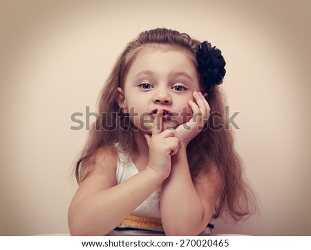 Cute kid girl showing silence sign the finger near lips. Vintage closeup portrait - stock photo