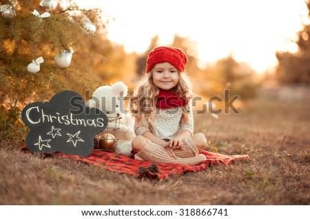 Cute kid girl sitting with christmas decorations outdoors. Wearing red knitted hat and scarf closeup. Celebrating christmas at meadow. Christmas tree decor. Smiling child. Merry christmas. Childhood.  - stock photo