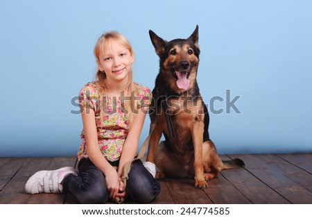 Cute kid girl sitting with pet dog in room over blue. Wearing casual clothes. Friendship concept. Togetherness.  - stock photo