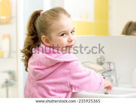 cute kid girl washing hands in bathroom - stock photo