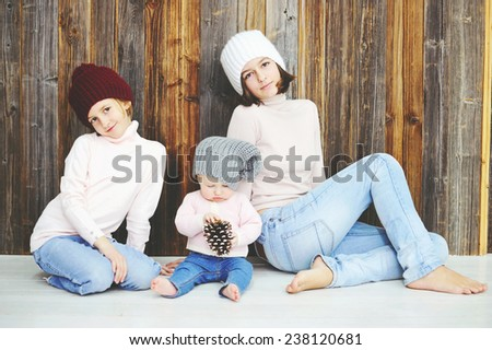 Cute kid girls of 10 month, 7 and 12 years old wearing knitted trendy winter hats and sweaters posing over wood wall - stock photo