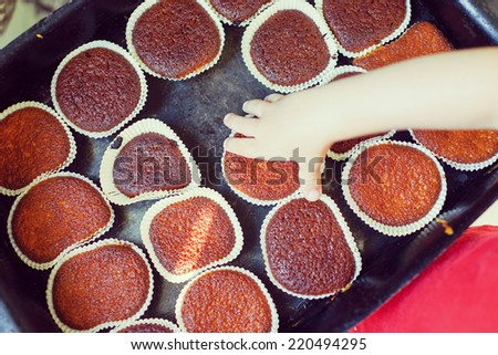 Cute kid helping in making cupcake with shallow depth of field - stock photo