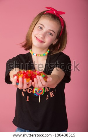 Cute kid holding a pile of colorful candy - stock photo