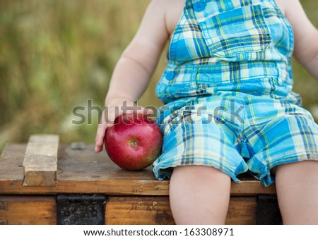 Cute kid holding a red apple in green park - stock photo