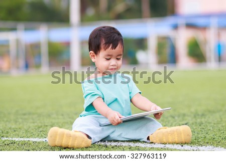 Cute kid holding tablet computer to learn or play game, education concept.