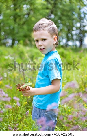 Cute kid holding wild strawberry outdoors