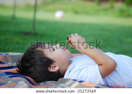 Cute kid is laying and eating fruit in beautiful environment - stock photo