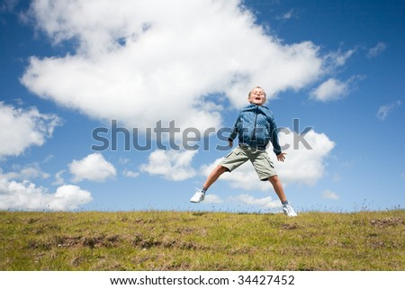 Cute kid jumping for joy in the air in a beautiful landscape with blue sky and fluffy clouds