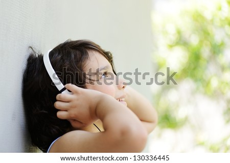 Cute kid listening to music on headphones and enjoying - stock photo