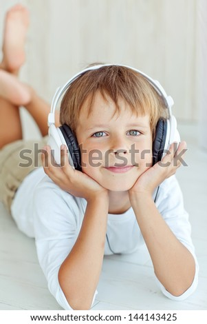 Cute kid listening to music on headphones and enjoying