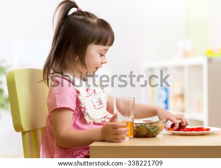 Cute kid little girl eating healthy vegetables at home