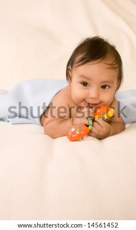 cute kid lying down on his tummy on blanket with stuck out tongue - stock photo