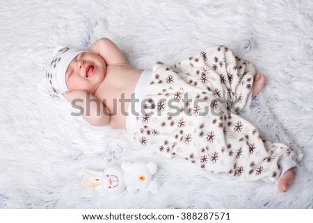 cute kid lying on his back. the baby is cries - stock photo