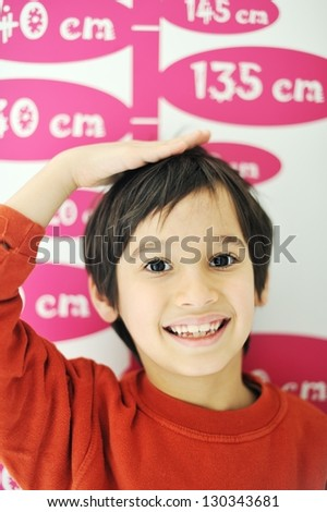 Cute kid measuring his height - stock photo