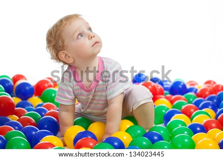 Cute kid or child playing colorful balls looking up - stock photo