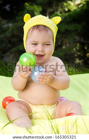 Cute kid playing colorful balls outdoors - stock photo
