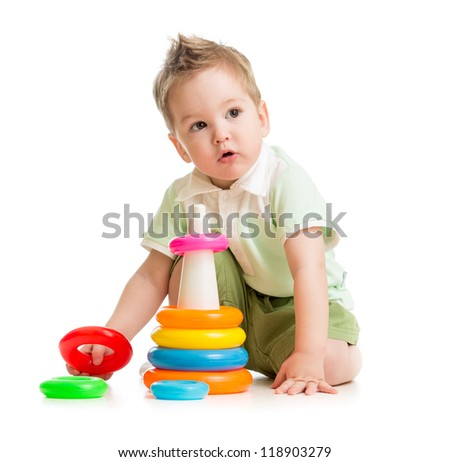 Cute kid playing colorful tower isolated on white - stock photo