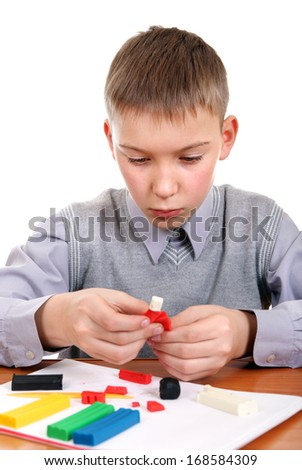 Cute Kid playing with colorful plasticine at the School Desk - stock photo