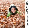 Cute kid playing with fallen leaves in a forest - stock photo