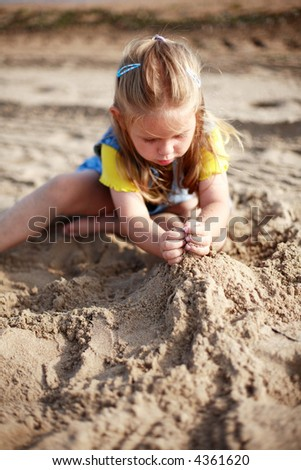 Cute kid playing with sand on a beach