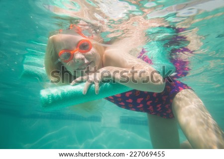 Cute kid posing underwater in pool at the leisure center