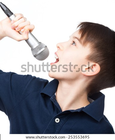 Cute kid singing holding microphone on white background - stock photo