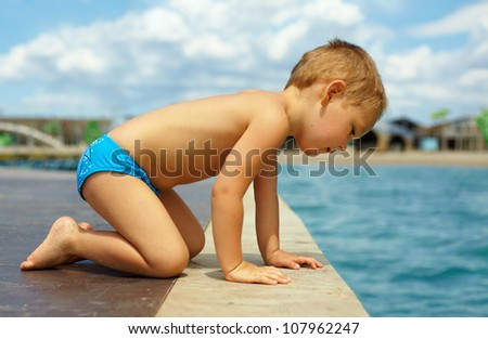 cute kid squats on pier, looks in water