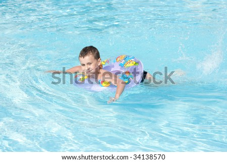 Cute kid swimming in a pool with clear water