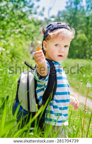 Cute kid with a backpack at nature - stock photo