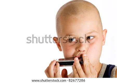 Cute kid with a bald head playing music on his harmonica. - stock photo
