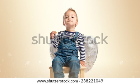 Cute kid with wings sit on wooden chair over ocher background  - stock photo