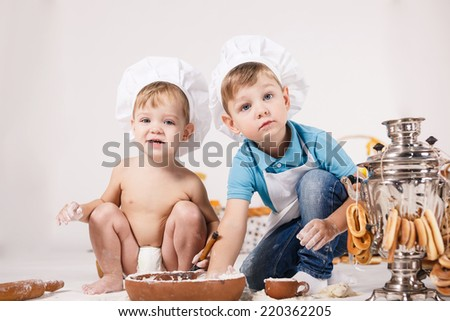Cute kids, adorable little girl and funny baby boy wearing chef hats playing with dough baking a pie in a sunny white kitchen