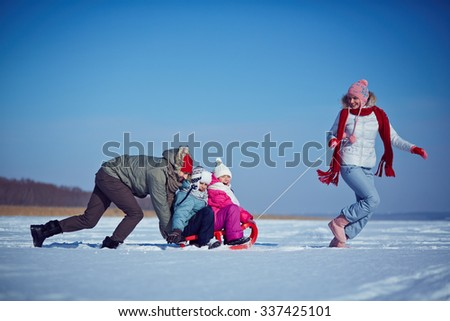 Cute kids and their parents riding on sledge on winter weekend - stock photo