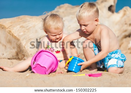 Cute kids. Brother and sister playing with sand at tropical beach