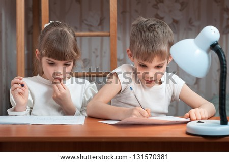 cute kids do their homework at the table - stock photo