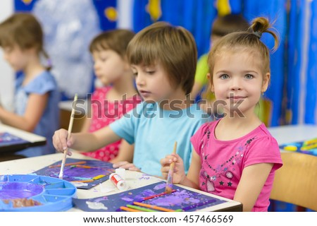 Cute kids doing their craft, painting at kindergarten - stock photo