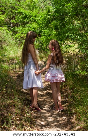 cute kids girls, sisters, girlfriends go on a forest path holding han